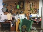 Peg board of hand tools, metal shelf and contents, desk, Dell laptop and more