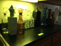 Various decanters, glassware, barware, wine glasses, white four tier shelf w/ gold accents