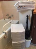 Bath towels, small white cabinet, plastic drawer storage bins, bath accessories, light, bath rail