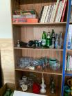 Al items on shelf-cookbooks, puzzles, glassware, candle holders, insulators, glass bottles