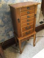 Small jewelry armoire measures 11 x16 x 39 and is a pressed wood oak style. Has 6 drawers, 2 side open doors and a lift top with mirror.