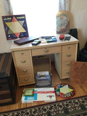 Small blond desk with games and typewriter-Pulitzer prize-winning novel has been started first page still in the typewriter