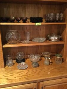 Various pieces of glassware/crystal include nine lavender sherbets, plates and goblets, serving bowls, plates, casserole dishes, canister with vintage metal lid, syrup dispenser