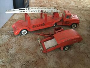 Two vintage toys. A firetruck and a pull-behind style combine.