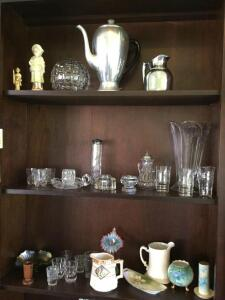 Contents of bookcase include vases, china, glassware, vintage silverplate coffee pot and pitcher . See all photos