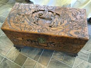 Lift top oriental design carved storage trunk. Measures 29 x 14 x 18