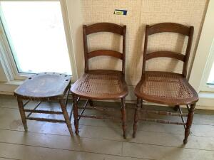 Two ladder back cane seat chairs and one chair that appears to function best as a stool now