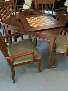 Square top game table measures 40 x 40 x 30 and has four spindle back chairs on casters