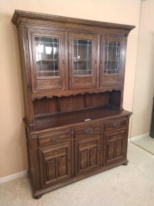 Two piece Ethan Allen hutch with upper leaded glass doors, three drawers and triple door lower storage Measures 55 x 19 x 76
