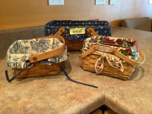 Three Longaberger handled baskets. One is marked Woven Memories two-all w/ protectors and liners