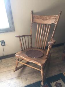 Vintage oak rocker with leather insert in seat (leather needs hooked down on one side), hand carved back