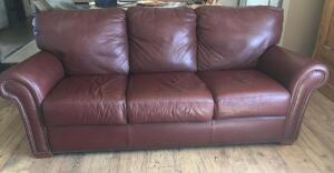 "Red/brown tone leather sofa 84"" long (nice condition, some scratch marks in center cushion, small tear in back upper corner)"