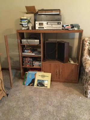 Entertainment center with assorted 45s, vinyls, 8 tracks, cassettes, DVDs, Montgomery Ward 4-in-1 turntable/cassette deck/8-track player/am/fm radio. Toshiba DVD player and Emerson VHS player also included. Center measures 48 x 15 x 42