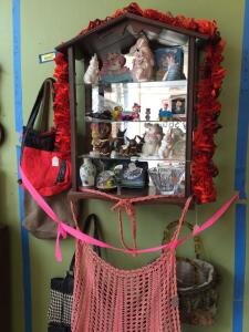 Shelf w bunny figurines, handbags, Peanuts, vintage crocheted apron, artwork Shelf measures 18 x 8 x 27