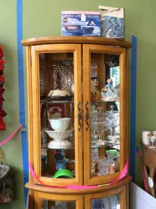 Curved front shelf and contents-Lenox, amber carnival glass, maracas, Wedgewood, Royal Haeger cookie jar, Wedgewood satin hen on nest Cabinet measures 12 x 29 x 72 Glass shelves are adjustable and glass front panels are available