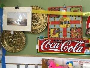 Artwork on wall-Coca Cola, tractor art, plates, **Boxes for 'Classy Lady' and 'Go For It' signs are sitting on metal shelf below**