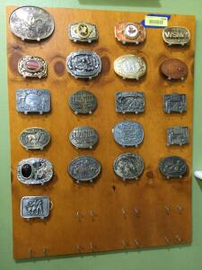 21 belt buckles on a handmade board-NFR, Frontier Hotel Las Vegas, Camp Courageous, and more.