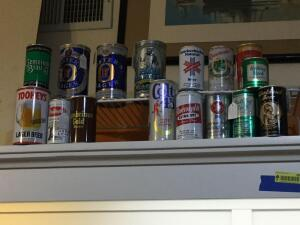 Many different types of beer cans and nautical wall art
