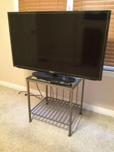 "46"" Samsung TV with remote and 22"" x 18"" x 24"" wrought iron glass-top stand."