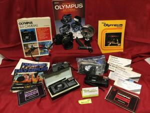 Olympus film cameras including an OM-2, PEN-EE, A11, A16, small tripod, and extras. See photos