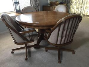 "Oak 52"" round pedestal dining table, 4 beige chairs on rollers (one chair has a few stains)"