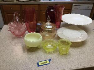Pretty glassware-Fenton satin bowl, two pink baskets, amber apple shaped snack plates, ruby red vase and glass, two pink vases w etched flower design, covered comport, two pieces vaseline glass and two pedestal cake stands. Chip on pieces shown.