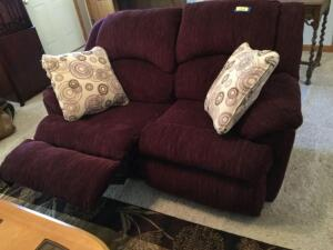 "Wine colored double reclining loveseat and pillows Measures 66""L"