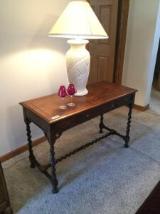 Walnut library table with single drawer and turned legs, table lamp and decor Measures 44 x 20 x 29