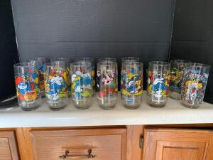 Eleven Smurfs glasses, two Muppets glasses and a Welch's Tyrannosaurus Rex jelly jar glass