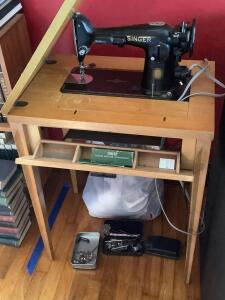 Singer pedal sewing machine in cabinet w accessories and a bag of craft supplies Measures 24 x 17 x 30 When open leaf adds add'l 24""