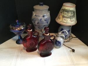 Modern gray stoneware salt glaze water cooler, small lamp, candle wick jug, two red glass bottles and a covered carnival compote
