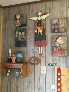 Various pieces of whimsical fairy art wall decor, an oak paper towel shelf, painted mason jar and more