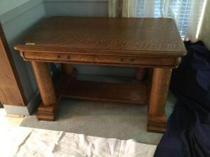 "Quarter-sawn oak library table with four round pillar corner legs in excellent condition. Measures 30""D x 48""W x 28""T. The top is a little sun-faded in one area where there was possibly a table cover"