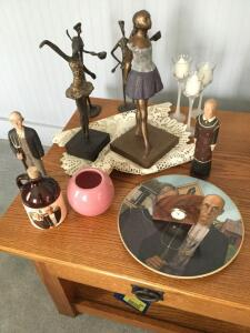 Variety of figurines includes ballerinas, a Grant Wood American Gothic plate, two figurines, a jug, a small walnut shelf clock and three candles