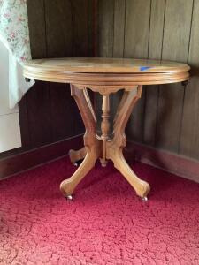 Walnut parlor table on casters Measures 36 x 37 x 29