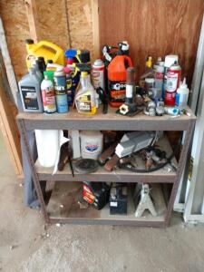 Three tier shelf with a variety of shop related items old small mower battery, pair of jack stands, partial jug of motor oil, engine oil, hand cleaner