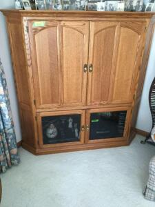 Mapleton brand oak veneer corner entertainment center. Contents on and in are excluded. Measures approximately 5' x 5'.