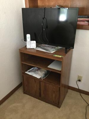32 inch Visio TV and Multi-purpose wooden cabinet, and contents, including three shelves of books on the wall.