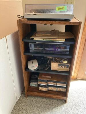 Cabinet with stereo equipment-Technics turntable, Sharp dual cassette deck, Sony discman car ready, Koss stereophones, two trays of cassette tapes and small stack of vinyls.
