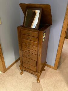 Modern oak jewelry armoire. Has two side swing doors and eight drawers. Measures 18 x 14 x 40. **NO CONTENTS**