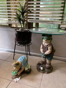 Iron stand w artificial plant, yard art and glass topped golfing frog table measures 18 x 22