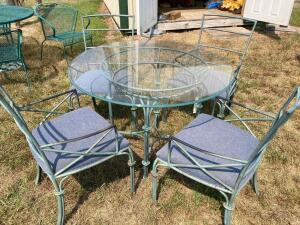 Four person patio table with glass table top and padded chairs