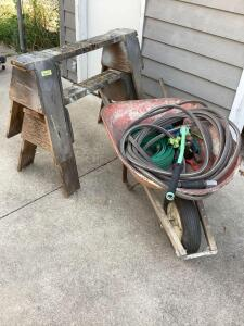 Two wooden saw horses, wheel barrow, two hoses and multiple nozzles
