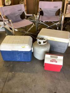 Coleman cooler, Igloo cooler, Igloo little playmate, one empty propane tank and two Coleman foldable camping chairs with side tables