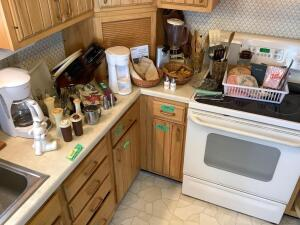 All items on the kitchen countertop include Mr. coffee coffee maker, Tupperware salt and pepper shakers, other miscellaneous salt and pepper shakers, knives in knife block, Oster electric can opener, Hamilton Beach blender, other kitchen utensils, storage