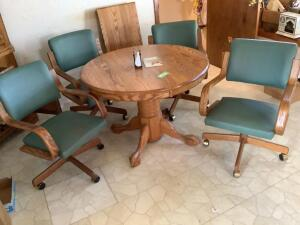 "Round 42"" oak kitchen table w/ one 18"" leaf and four vinyl padded dining chairs with arms and on wheels"