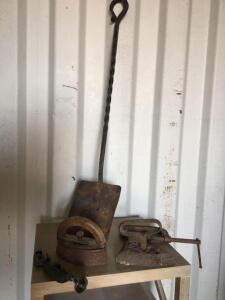 A pair of sad irons, C-clamps and coal shovel