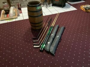 Nail keg holding two Whitetails Unlimited pool cues with cases, wood handled putter, Montrose Special wood handled iron, MacGregor wood handled mid iron and another wood handled iron