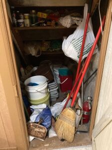 Utility closet full of useful items such as brooms, mops, electric cords, buckets, busboy tubs, tools, charcoal