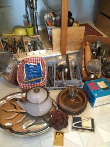 Large variety of silverware, kitchen utensils including strainers, rolling pins, two or three sets of flatware, nice basket with liner and more
